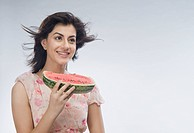 Woman eating watermelon and day dreaming