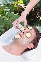 Beautician putting cucumber slices on a man´s face
