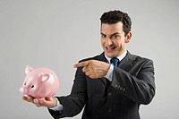 Portrait of a businessman pointing at a piggy bank