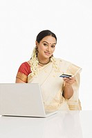 Woman holding a credit card and working on a laptop