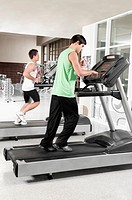 Two men running on treadmills