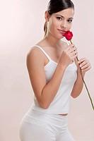 Portrait of a woman smelling a rose
