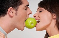 Couple biting into a green apple