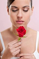 Close_up of a woman smelling a rose