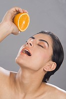 Close_up of a woman squeezing juice from a half of orange in her mouth