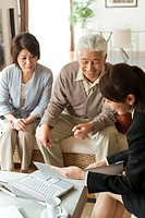 Young businesswoman showing file to senior couple