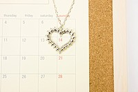 Necklace with heart pendant on calendar, close up