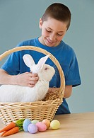 Young boy petting a rabbit in Easter basket