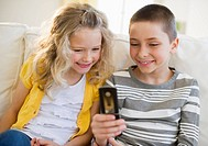 Siblings looking at cellular phone