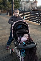 A boy pushes his sister in a stroller through Riverfront Park, Spokane, Washington, USA