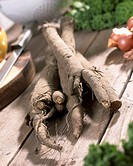 Greater burdock roots Arctium lappa on wooden table