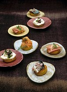Potato canapes with meat in aspic, salmon, herring and goat´s cheese