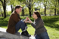 Man proposing to woman on a beautiful sunny day in a park