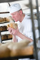 Baker smelling fresh bread from oven