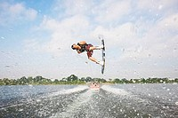 Young man performing wakeboarding stunts