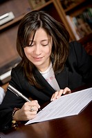 business woman signing a contract in her office _ focus is on her right hand therefore text of the letter is not readable