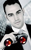 business search _ confident man in a corporate environment holding binoculars
