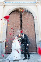 A just married couple coming out of the church with people throwing rice and rose petals to them.