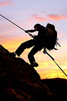 rock climber at sunset going up a mountain