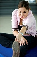 beautiful woman at the gym smiling doing stretching exercise
