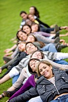 happy group of friends lying on the grass outdoors in a park