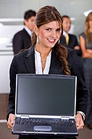 business woman with a laptop in an office smiling
