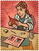 A woman cutting papers and creating a scrapbook