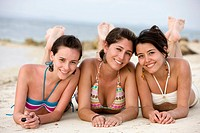 Teenage girls at the beach _ smiling while lying on the floor .