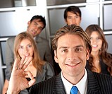 businessman doing the ok sign smiling with his team behind him