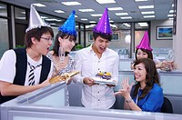 Colleagues wearing headwear and holding a cake for celebrating