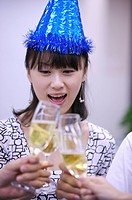 Young woman wearing headwear and toasting with other people