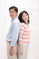 Couple, Couple standing of back to back and looking at the camera with smile (thumbnail)