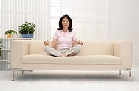 Wife, Woman making lotus position on sofa with eyes closed