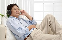 Husband, Man lying on sofa and listening music with smile