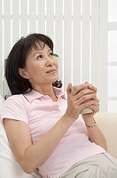 Wife. Woman holding a cup and looking up with smile (thumbnail)