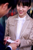 Young woman delivering name card to young man and smiling
