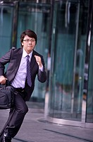 Young businessman holding briefcase and running