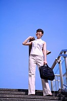 Young woman standing on a staircase, holding briefcase and looking up with smile