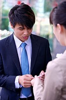 Young woman and man delivering name card together