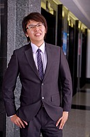 Young businessman standing with hands in pockets and smiling at the camera