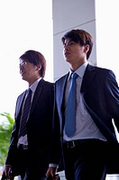 Two businessmen walking and looking away together