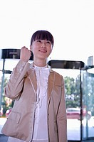 Young woman looking up and smiling with fist up