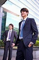 Two businessmen standing with hands in pockets and looking away with smile