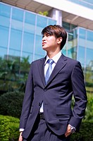 Young businessman standing with hand in pockets and looking up