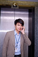 Young businessman holding mobile phone and standing before elevator