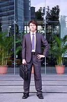 Young businessman holding briefcase and standing with arms akimbo