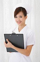 Young nurse holding clipboard and smiling at the camera (thumbnail)