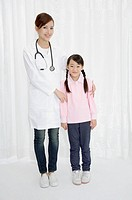Female doctor and little girl standing and looking at the camera together