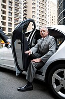Senior businessman getting off the car and looking at the camera
