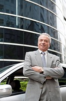 Senior businessman standing near the car with arms crossed and smiling